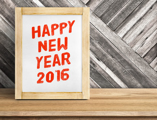 Happy New Year 2016 word on wood frame on table and diagonal pla