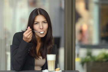 Woman savoring a tasty cup of cappuccino coffee