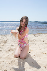 Pretty girl, happy on the beach in a swimming suit