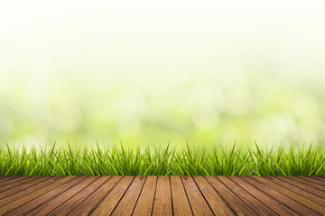 grass with green blurred background and wood floor Wall mural