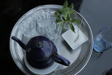 Blue teapot, sugar container, mint leaves, empty glasses and sugar container sit on a tray 4690