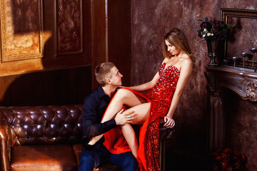 Beautiful young woman in red dress is flirting with elegant man