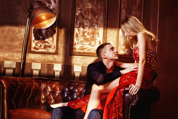 Beautiful glamour young couple is flirting in bedroom