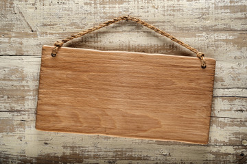 light wood signboard on rustic wooden wall