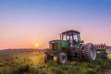 Tractor in a field on a Maryland farm at sunset Fototapete
