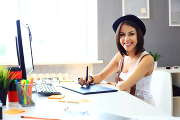 Young female designer using graphics tablet while working