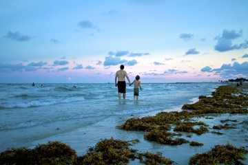 Father and son walking on the beach at sunset, South Beach Florida
