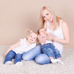 Happy family playing on floor. Mother with children sitting on fluffy carpet in room. Motherhood. Looking at camera.