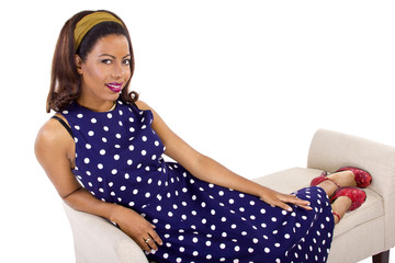 retro black female wearing a vintage blue polka-dot dress on a chaise