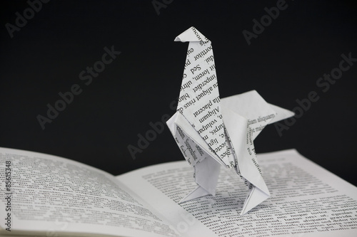 Origami dinosaur coming out of a book
