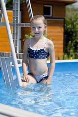 Child girl in blue bikini near swimming pool. Hot Summer