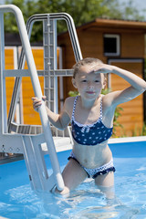 Child girl in blue bikini near swimming pool. Hot Summer