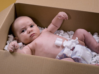 Baby, three months old, inside a cardboard box with polystyrene chips.