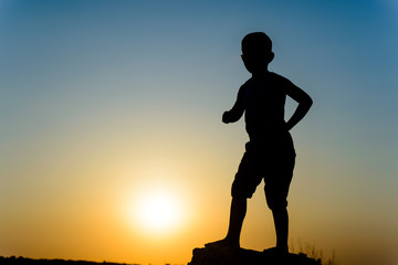 Small boy silhouetted by a colorful sunset