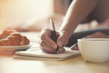 female hands with pen writing on notebook with morning coffee an