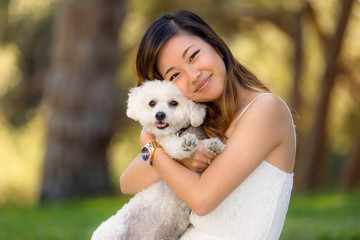 Beautiful woman with white dog smiling and hugging at the park