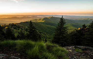 The warm colors of the spring blooms in the Blue Ridge mountains illuminate the landscape as the sun comes up in the morning.