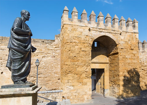 Cordoba - The statue of philosopher Lucius Annaeus Seneca the Younger by Amadeo Ruiz Olmos (1913 - 1993) and medieval gate Puerta del Almodovar.