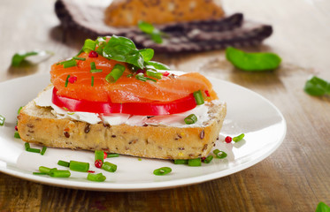 Sandwich with cereals bread and salmon on old wooden background.