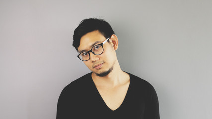 A man with eyeglasses is looking at camera with easy pose.