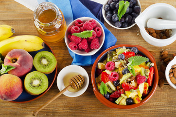 Healthy homemade fruit salad, fresh berries and fruits on   a wo
