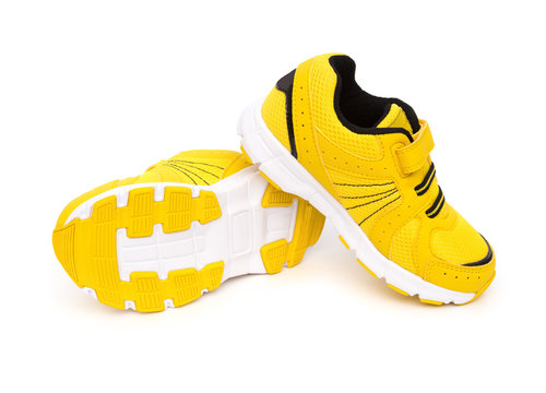 pair of yellow sporty shoes for kid on a white background