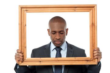 Sad businessman with wooden frame