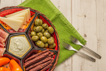 Basket with several Spanish tapas on white table