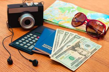 Travel set: passport, money, mobile phone, blank notebook, camera, road map, sunglasses, calculator, headphones. Summer accessories.
