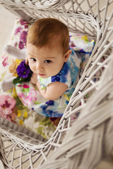 little girl sitting in a wicker chair. view from above