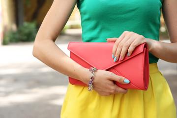 Wall Mural - Outdoor fashion girl with coral orange handbag clutch