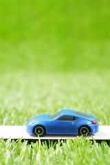 緑の草原を走る青いスポーツカー