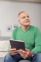 älterer mann sitzt auf dem sofa und hält tablet in der hand