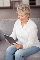 seniorin liest am tablet-pc zu hause