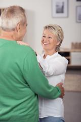 glückliches älteres paar umarmt sich zu hause