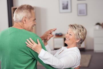 glückliches, älteres paar tanzt zuhause