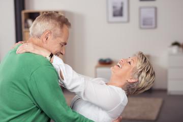 glückliche senioren tanzen durch das wohnzimmer