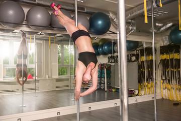 Pole dancer performing closed bridge
