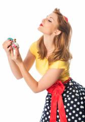 Frau im Rockabilly Style besprüht sich mit Parfüm