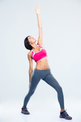 Full length portrait of a sporty woman stretching