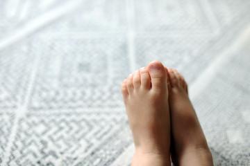 kinderfüße vor grauem teppichhintergrund