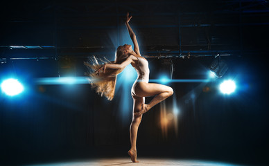 Sexy ballerina on stage posing against the backdrop of the spotl