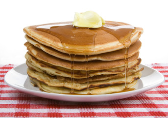 Big Stack of Pancakes – A huge stack of pancakes, covered with maple syrup and butter. On a white plate and red checked tablecloth in background.