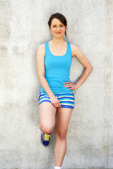 Girl in blue tank top and shorts over the wall smiling.