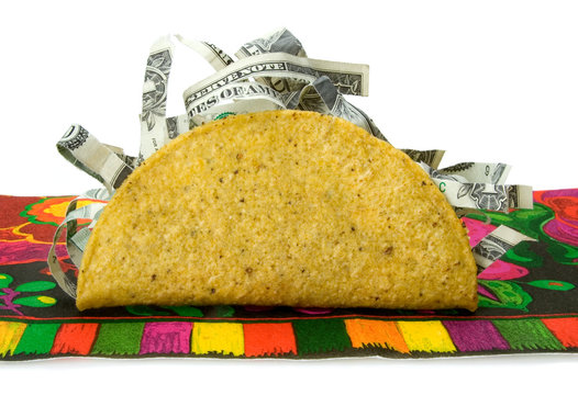 Colorful Money Taco – Concept image for high price of food or low price of food. Shredded money sticking out of taco shell. On a colorful tablecloth.