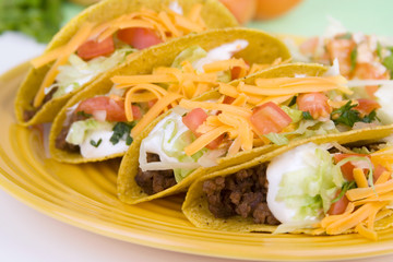 Four Beef Tacos on a Plate with Sour Cream, Cheese and Tomatoes