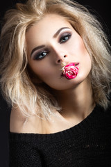 Beautiful blonde girl with dark makeup with a flower in her lips.