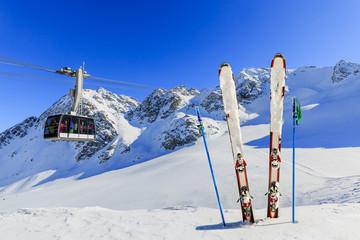 Skiing - mountains, cable car and ski equipments on ski run