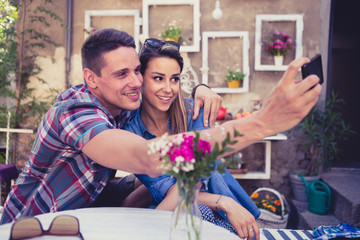 Young happy couple at cafe taking selfie