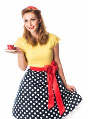 Frau im Rockabilly Style bietet eine Tasse Kaffee an